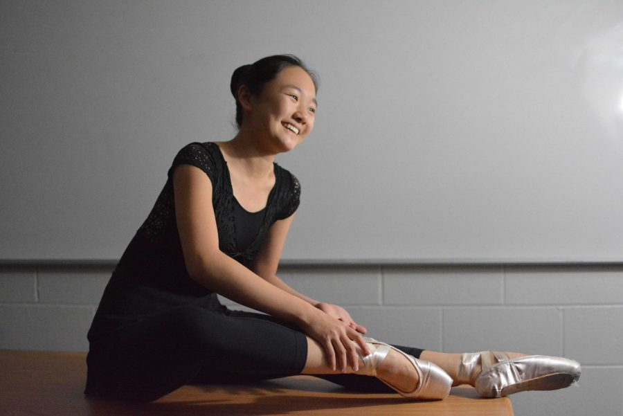 Angel Hoyang '18 ties the ribbons on her pointe shoes as she dresses for rehearsal. Credit: Kate Schrage '18/Chronicle