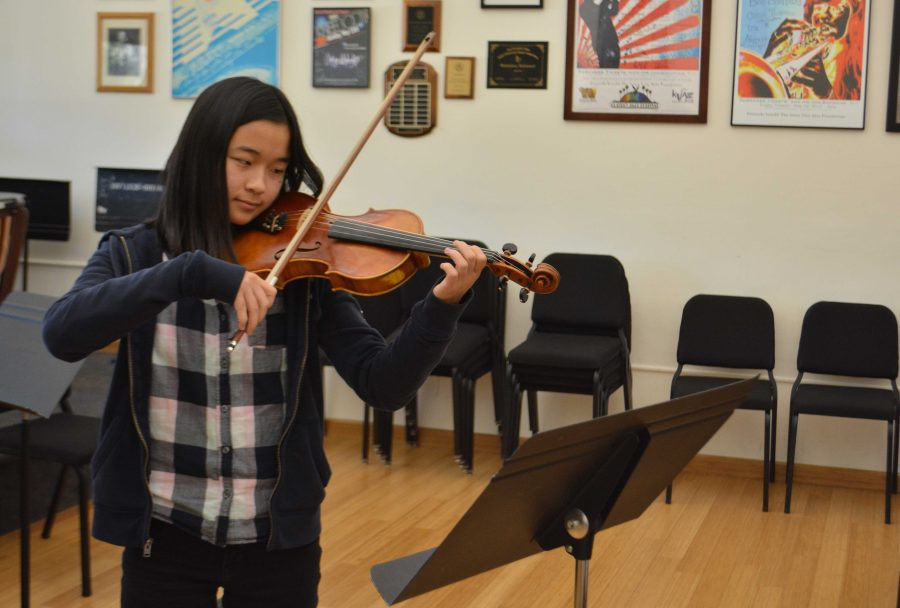 Anna Gong '18 practices a violin solo in the orchestra room. Credit: Claire Dennis/Chronicle