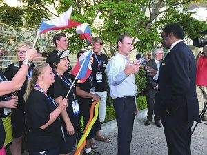 Hot Off The Press: President of Harvard-Westlake School Rick Commons talks to a CBS2 reporter about hosting the Special Olympics athletes. Men and women representing the Cuban teams stand behind him. (Photo courtesy of Stacy Marble.)