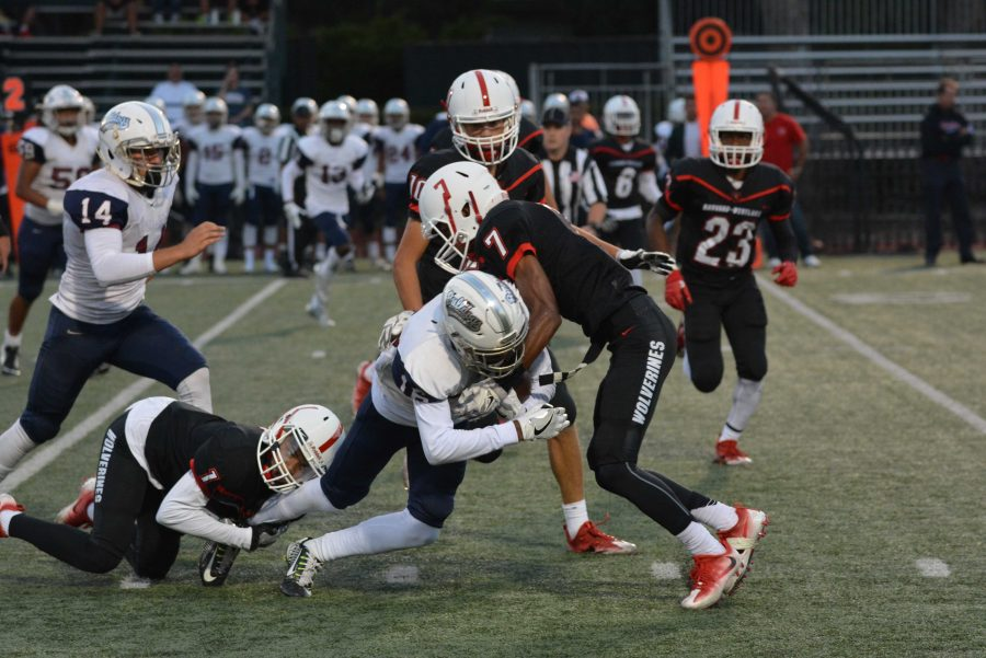 Max Robertson '17 tackles a Garfield player during the Wolverines' 31-38 loss on Sept. 9.  Credit: Cameron Stine/ Chronicle