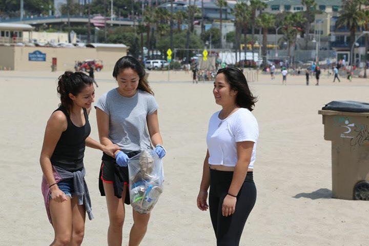 Justine Barraza '17, Sydney Tsutsui '17 and Stephanie Desoto '17 clean up trash in Santa Monica Beach. Printed with permission of Eitan Sneider.