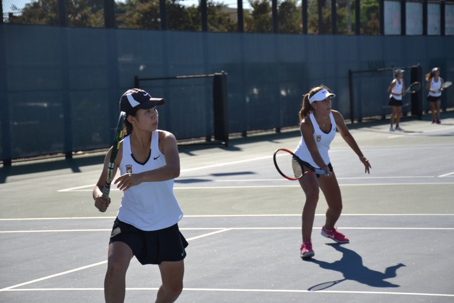Girls' tennis team players swing in a match versus Notre Dame. Photo Credit: Elly Choi / Chronicle