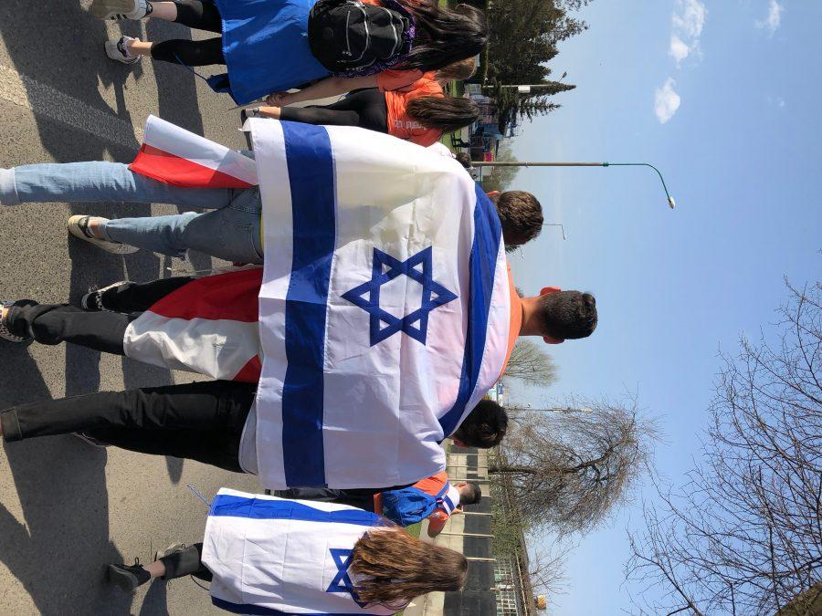 Students march with the Israeli flag on their backs at the March of the Living, an event that serves to educate students about the history of the Holocaust. Attendees travelled to Poland and Israel as part of the program for two weeks. Printed with permission of Jack Cohen '18