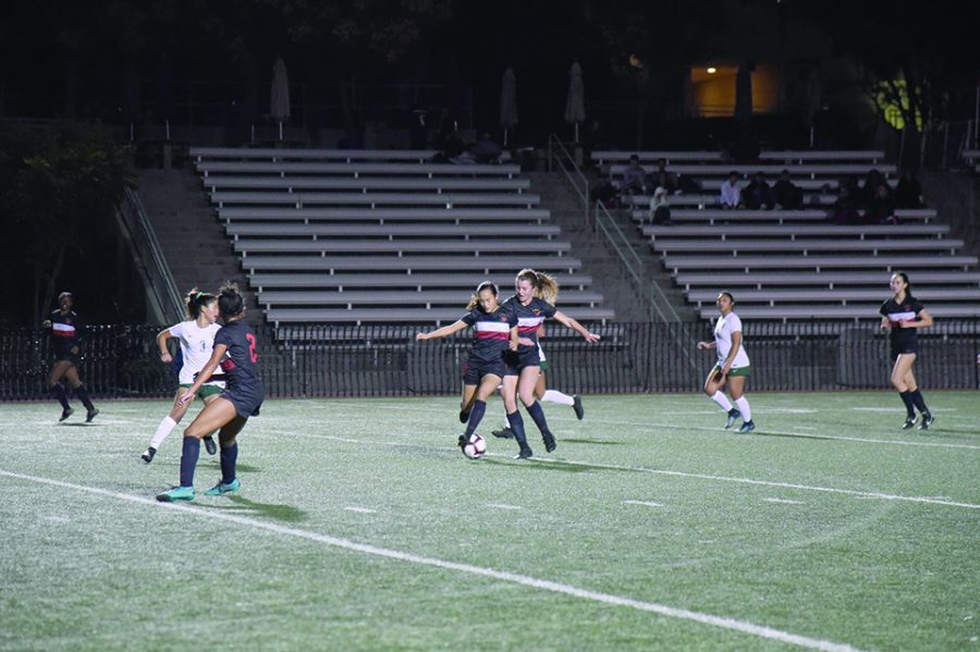 Midfielder Natalie Barnouw '21 and midfielder Whitney Elson '19 both go after the ball in the Wolverines' 2-2 game against South Hills High School on Dec. 4. Credit: Ryan Albert / Chronicle