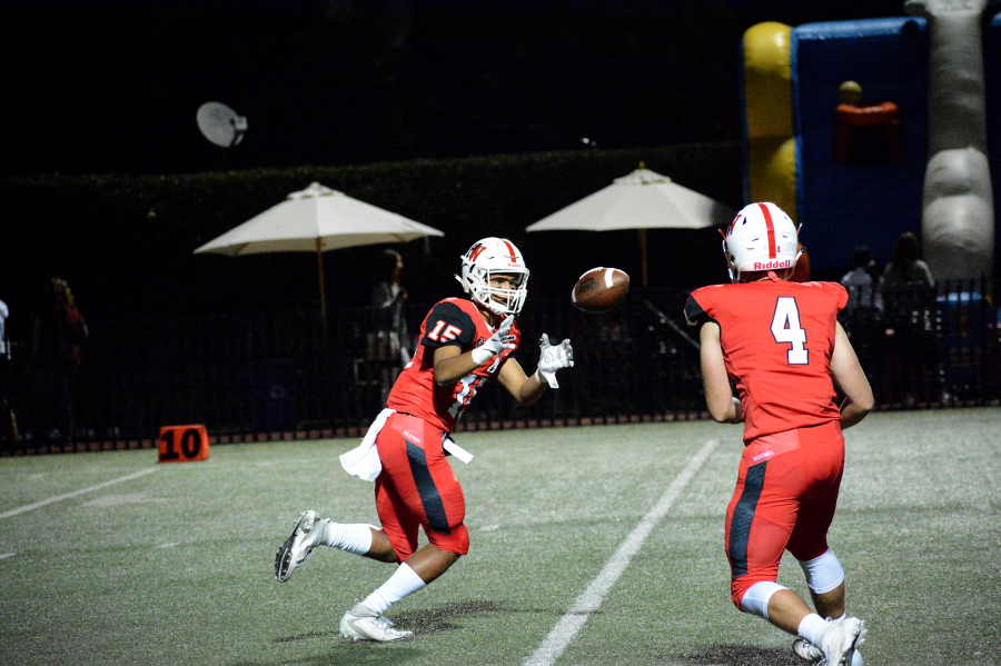 Wide Receiver AJ Holmes '22 catches a pitch against St. Genevieve High School. The Wolverines won 27-21.