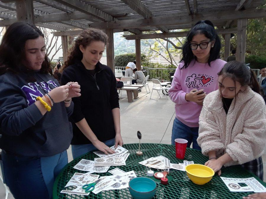 Maddie Boudov '21, Community News Editor Sarah Healy '20, Rachel Tan-Goldhammer and Chronicle Layout Assistant and Staff Writer Sarah Mittleman '22 engage in activities such as henna decorating. Credit: Tanisha Gunby/Chronicle