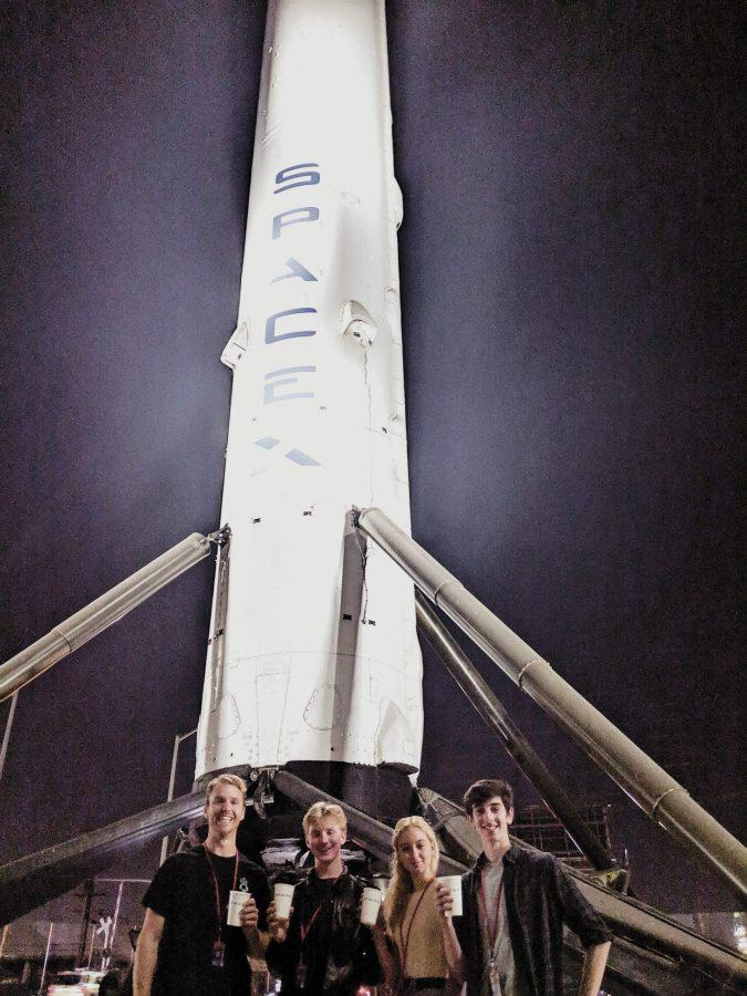 Robotics teacher Andrew Theiss, Erik Anderson '20, Page Clancy ' 22 and Dean Reiter '20 pose in front of the SpaceX rocket with their new SpaceX logo cups in hand. Credit: Printed with permission of Andrew Theiss