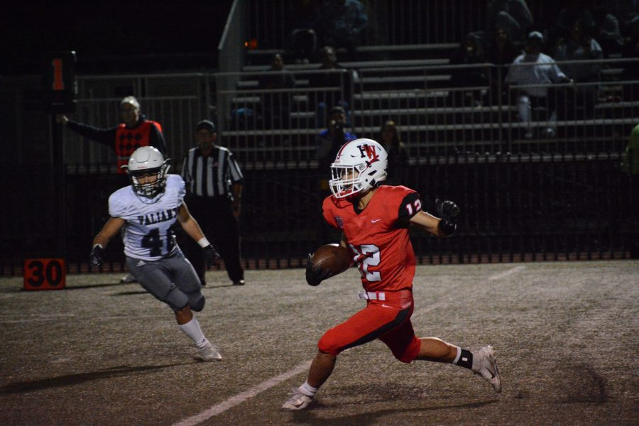 Wide reciever Mark Cho '22 surveys the field while returning a kickoff at home against league opponent St. Genevieve High School on Oct. 12. The Wolverines eon the homecoming match 27-21, bringing their league record to 2-2.