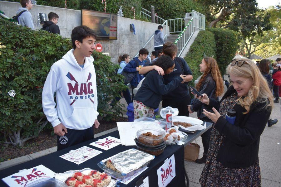 Upper School Dean Sharon Cuseo and Eli Friedman '21 converse at the Winter Market on Dec. 2. In addition to selling food at the sale, many students chose to sell an assortment of goods, such as crocheted hats, handmade pottery and bracelets. Credit: Frank Jiang/Chronicle