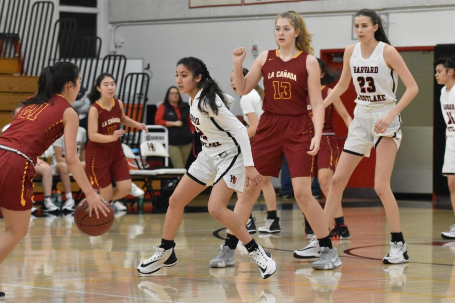 Guard Paula Gonzalez '21  reads the ball screen and defends the opposing player in a 75-31 win against La Canada High School in the Brentwood Invitational. Credit: Jaidev Pant/Chronicle
