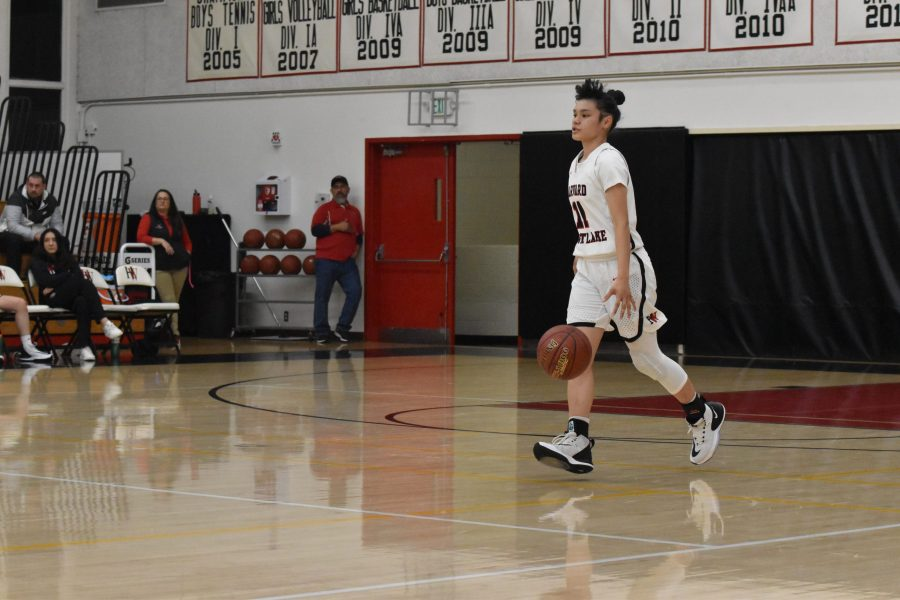 Guard Melissa Zozulenko '21 dribbles the ball up the court in a 75-31 win against La Canada High School in the Brentwood Invitational. Zozulenko made the game-winning free throw for the Wolverines against Chaminade High School