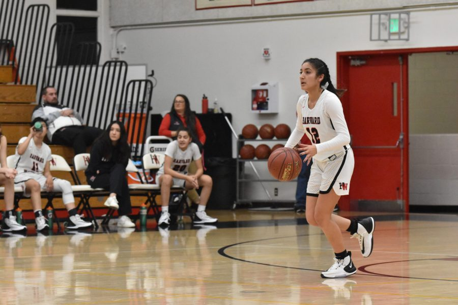 Guard Paula Gonzalez '21 surveys the court for teammates in a 75-31 win against La Canada High School in the Brentwood Invitational on Dec. 7. Credit: Jaidev Pant/Chronicle