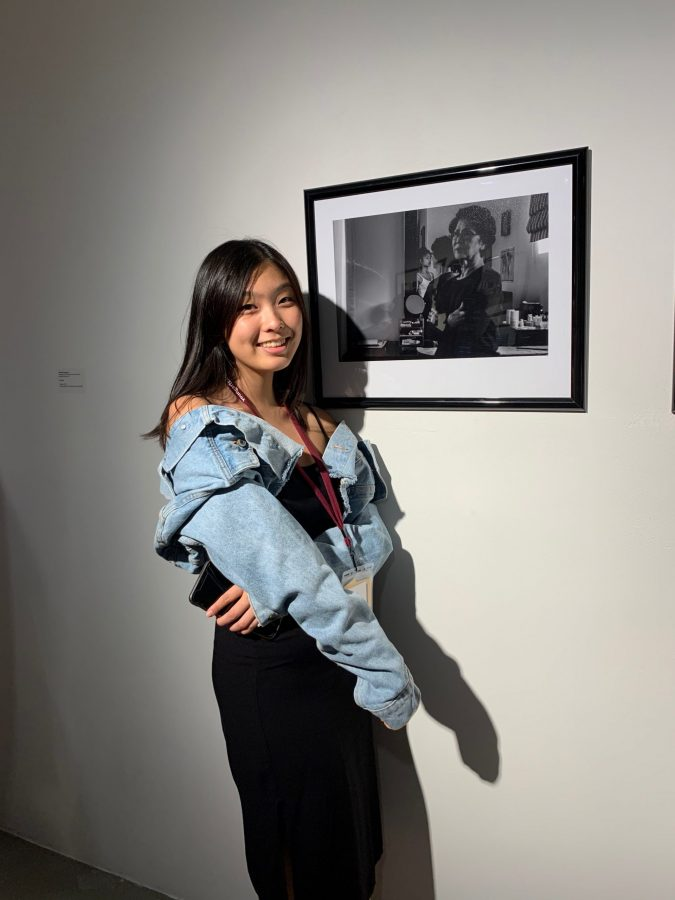 """Chronicle Photography Editor Caitlin Chung '20, who was recently named a U.S. Presidential Scholar, poses in front of her photograph """"Third Generation"""" during National YoungArts Week in Miami on Jan. 10. Photo credit: Printed with permission of Caitlin Chung"""