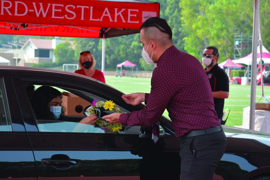 Mohona Ganguly '21 receives a floral wreath from upper school dean Celso Cárdenas from inside her car. The celebration was held for seniors as a drive-thru due to the coronavirus Sept. 13. Credit: Crystal Baik