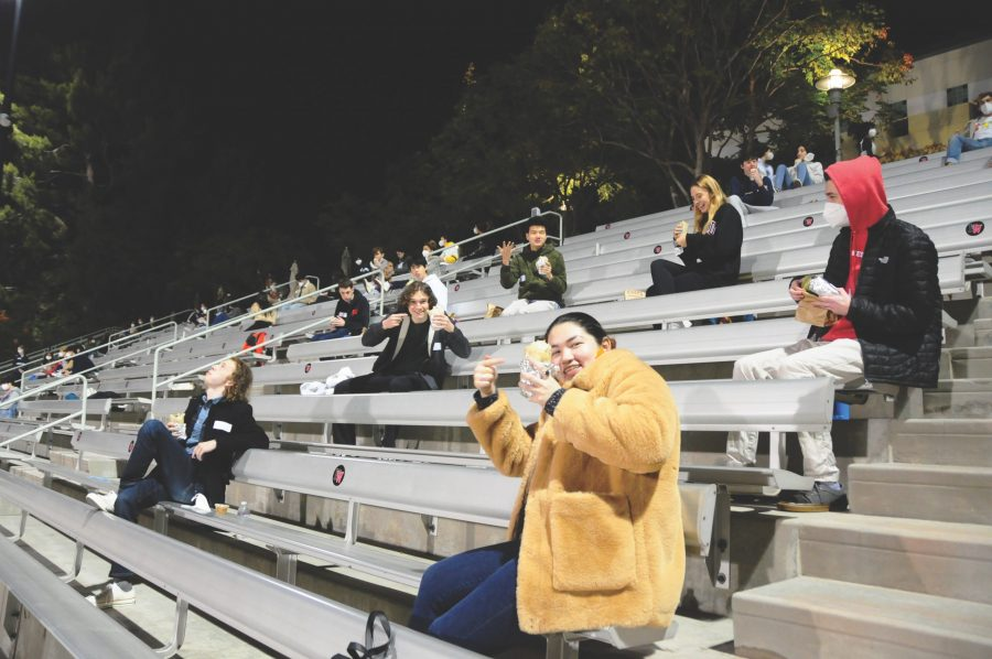 Clockwise from bottom right) Felicity Phelan '21, Ford McDill '21, Will Lake '21, Matthew Lee '21, Alexandria Lange '21 and Chronicle Editor-in-Chief Ethan Lachman '21 eat a socially-distanced meal together and chat about their senior year experiences on the bleachers next to Ted Slavin Field on Nov. 13.  Photo Credit: Hannah Han/Chronicle