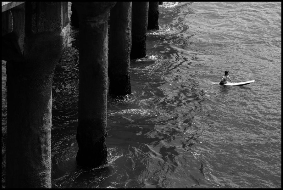 A black-and-white photograph taken by Baxter Chelsom '23 shows a surfer paddling out on his board in an attempt to catch a wave.