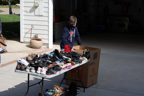 Wilson Federman '24 sorts through piles of shoes donated from local students.