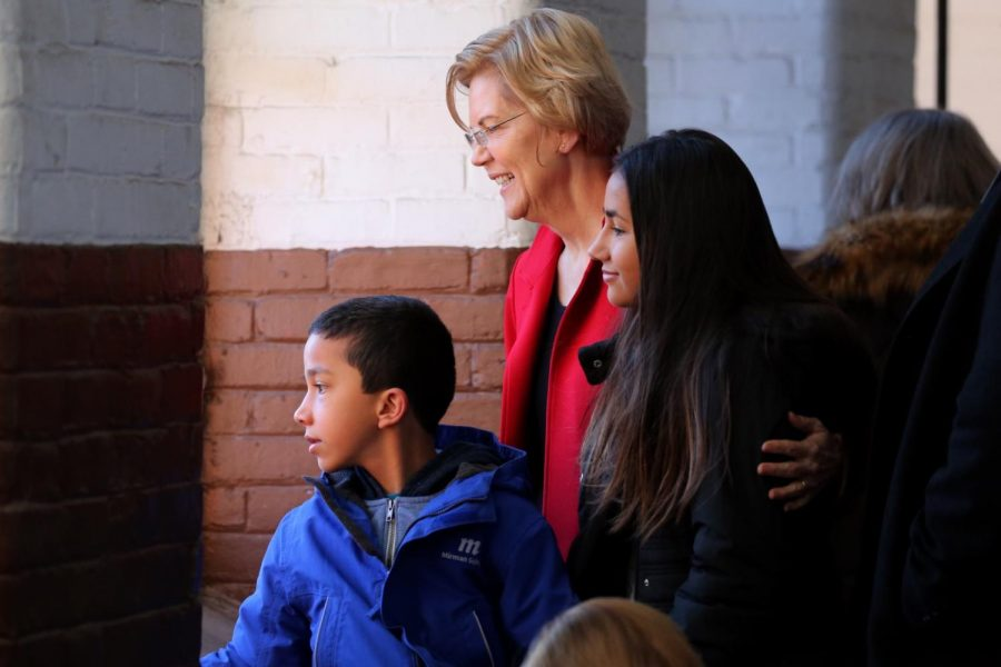 (From left to right) Atticus Tyagi, Senator Elizabeth Warren and Lavinia Tyagi '23 embrace with a smile as they pose for a photo.