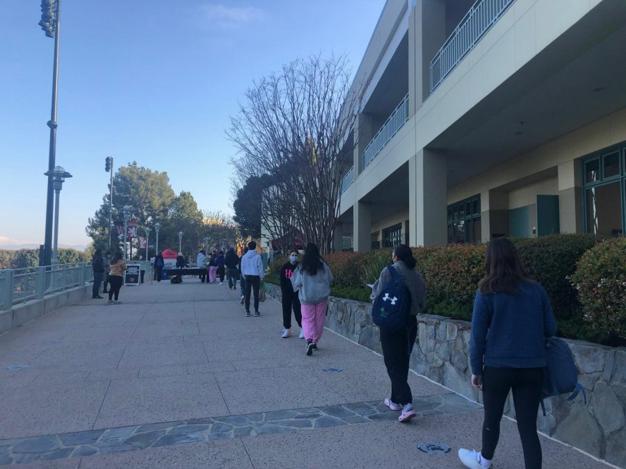 Students keep social distance between themselves while standing in line to register for their SAT tests.