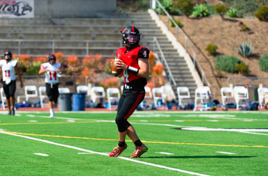 Quarterback+Marshall+Howe+%2721+warms+up+by+throwing+passes+to+his+teammates+before+the+scrimmage+against+Brentwood+School.+