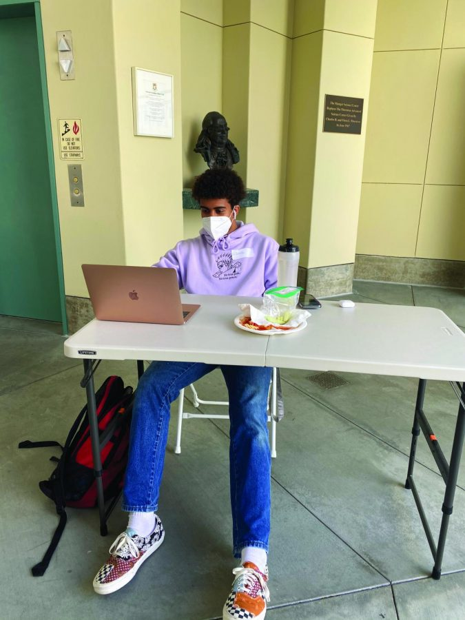 Prefect Jason Thompson '22 completes his homework for the day and eats lunch from the cafeteria. He wears the KN95 mask provided to him by the school while sitting near Munger Science Center on March 15.