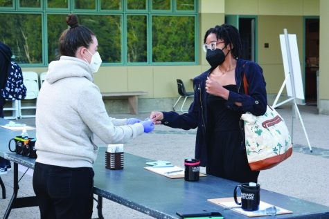 A Daily Dose: Chandace-Akirin Apacanis '21 gives her nasal swab to Upper School Nurse Becca Pilgrim for pooled testing outside of the Munger Science Center in adherence with COVID-19 protocols before her class.