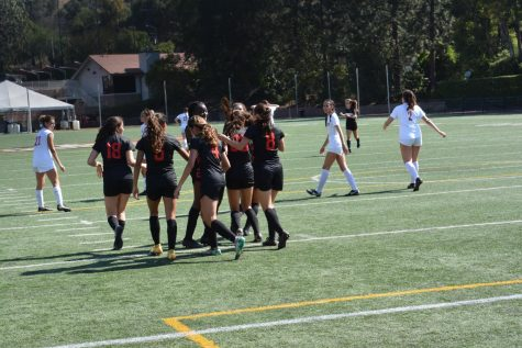 The squad embraces after a goal at Ted Slavin Field in a game against San Clemente High School on May 14.