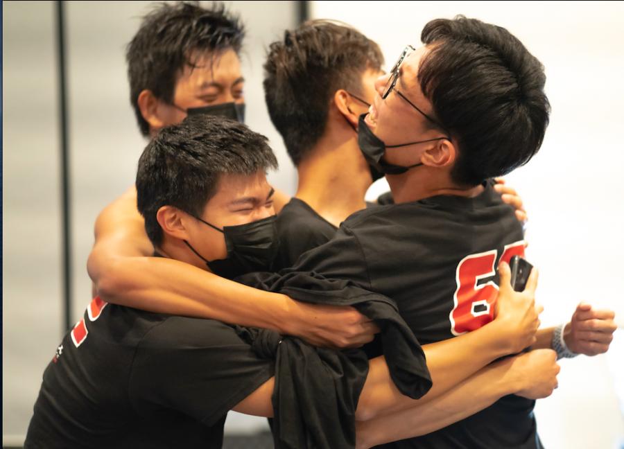 Members of school robotics team 62B embrace after winning the 2020 Live Remote VEX Robotics World Championship.