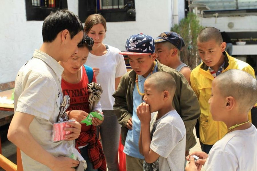 Cami Katz '16 (third from left) passes out candy to visually-impaired children at a Tibetan school as part of her volunteer work for a summer fellowship. Credit: Cami Katz, used with permission