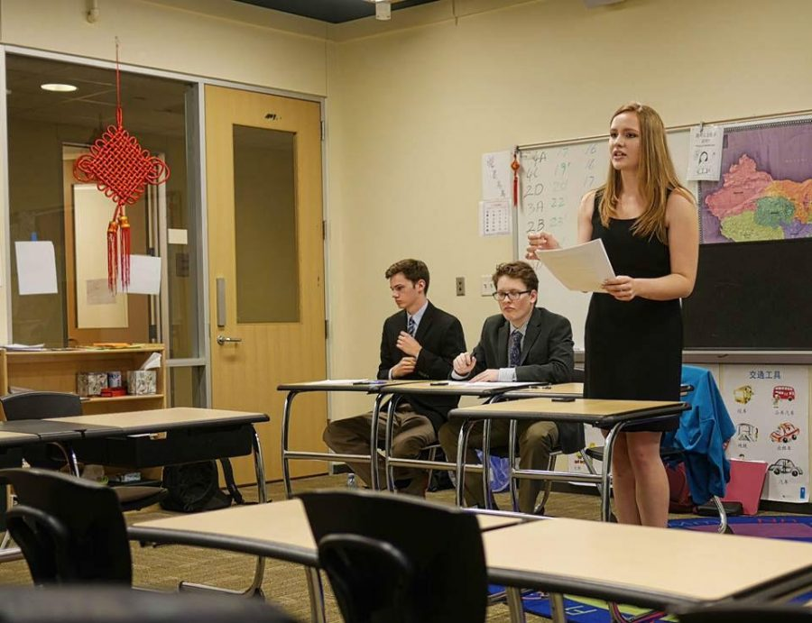 Liz Yount '17 speaks during a World Schools debate at the Greenhill Fall Classic as teammates Aidan Luscinski '17 and Alec Winshel '16 listen. The team took second place at the tournament.