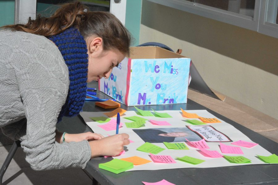 Carmen Levine '17 writes a message to pay tribute to science teacher Jim Brink on the anniversary of his passing. Credit: Jesse Nadel/Chronicle