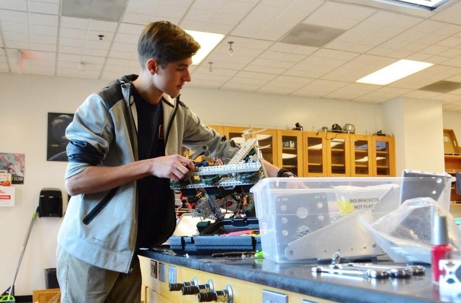Cameron Schiller '18  works on his robot, preparing it for the next VEX world robotics competition.  Credit: Maddy Daum/Chronicle
