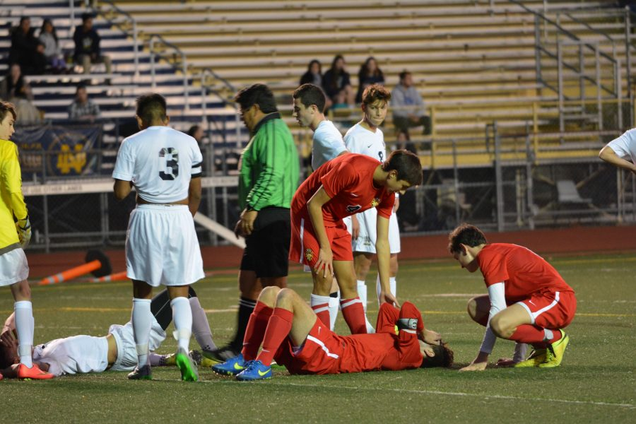 Max Rolnick '16 lies on the ground after crashing into a player in the Wolverines' 1-1 tie against Notre Dame.  Credit: Jake Liker/ Chronicle