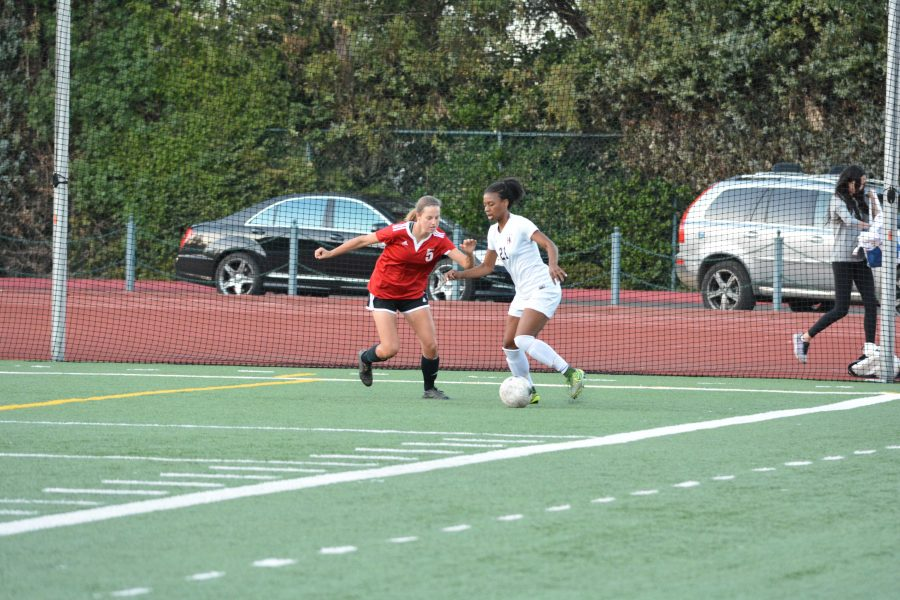 Courtney Corrin '16 dribbles around a Lakewood defender in the first round of CIF playoffs.