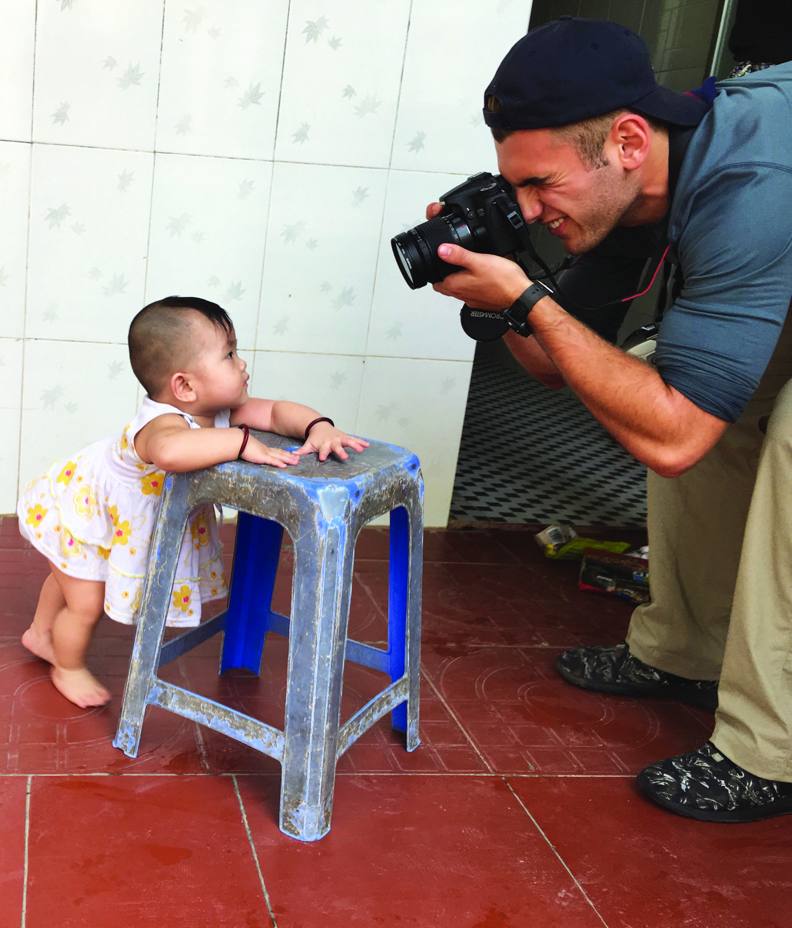 CAM AND HIS CAM: Cameron Welther '17 photographs an infant at a Buddhist orphanage just outside of Saigon. Welther and 15 other students handed out toys and played with the children there. The orphanage was one of the many sites in Vietnam that the students who were on the Digital Storytelling Adventure trip visited. Credit: Lauren Kim/Chronicle