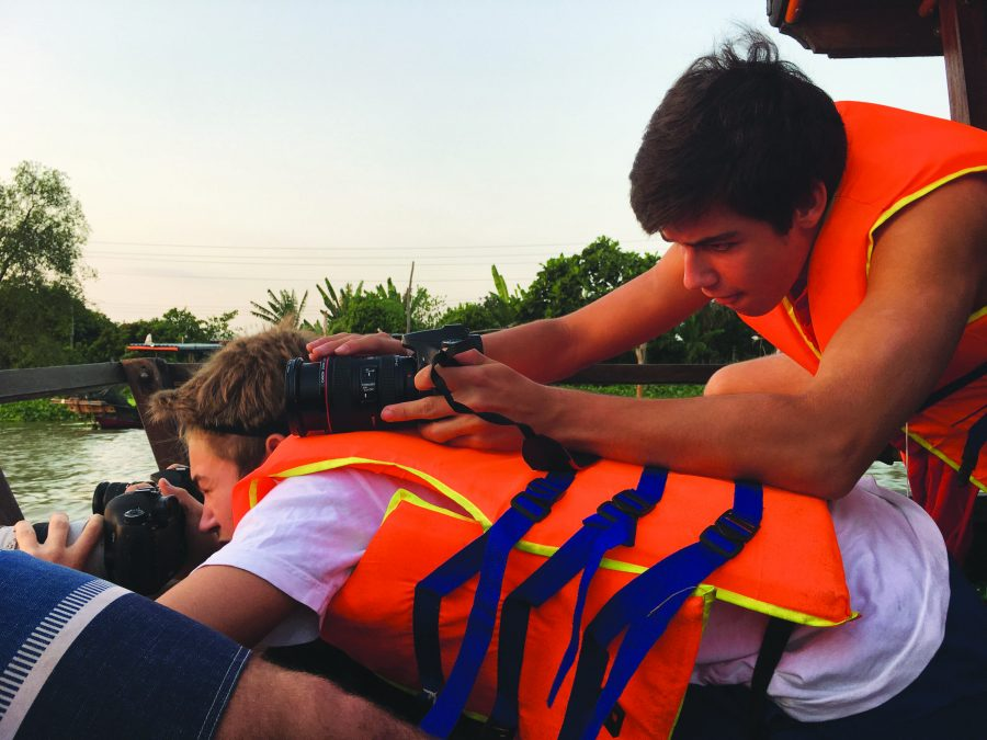 LENDING A HELPING SHOULDER: James Kanoff '17 leans on Chance Washburn '18 in order to capture a picture of the sunset in Vietnam. Students traveled there for over a week to work on digital media projects independently and in groups. Credit: Lauren Kim/Chronicle