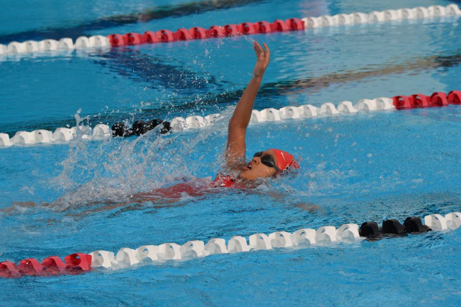 A swimmer backstrokes during the season opening victory over Orange Lutheran on March 3.