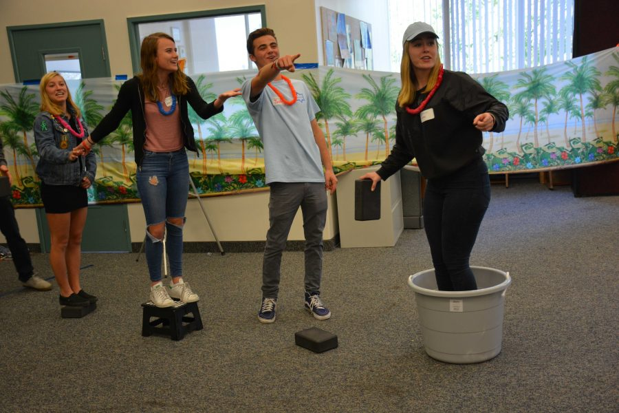 Rasa Barzdukas 17, Jean Sanders 17 and Lola Clark 17 attempt to cross to the other side of Chalmers Lounge without touching the floor during the activity Escape from Paradise. Josh Musicant 17, a student enrolled in the Unconventional Leadership class, runs the activity, making sure attendees follow the rules. Credit: Teresa Suh/Chronicle
