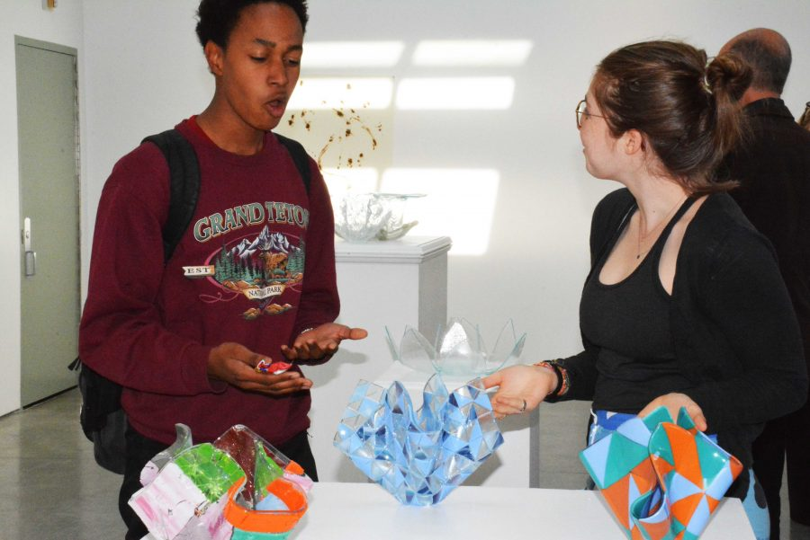 THROUGH THE GLASS: Miles McQueen '16 and Mady Schapiro '16 talk about the featured glass sculptures displayed in the Feldman-Horn Gallery. The visual arts department recently bought a glass-blowing furnace that the students have been using. Credit: Sophie Cohen/Chronicle