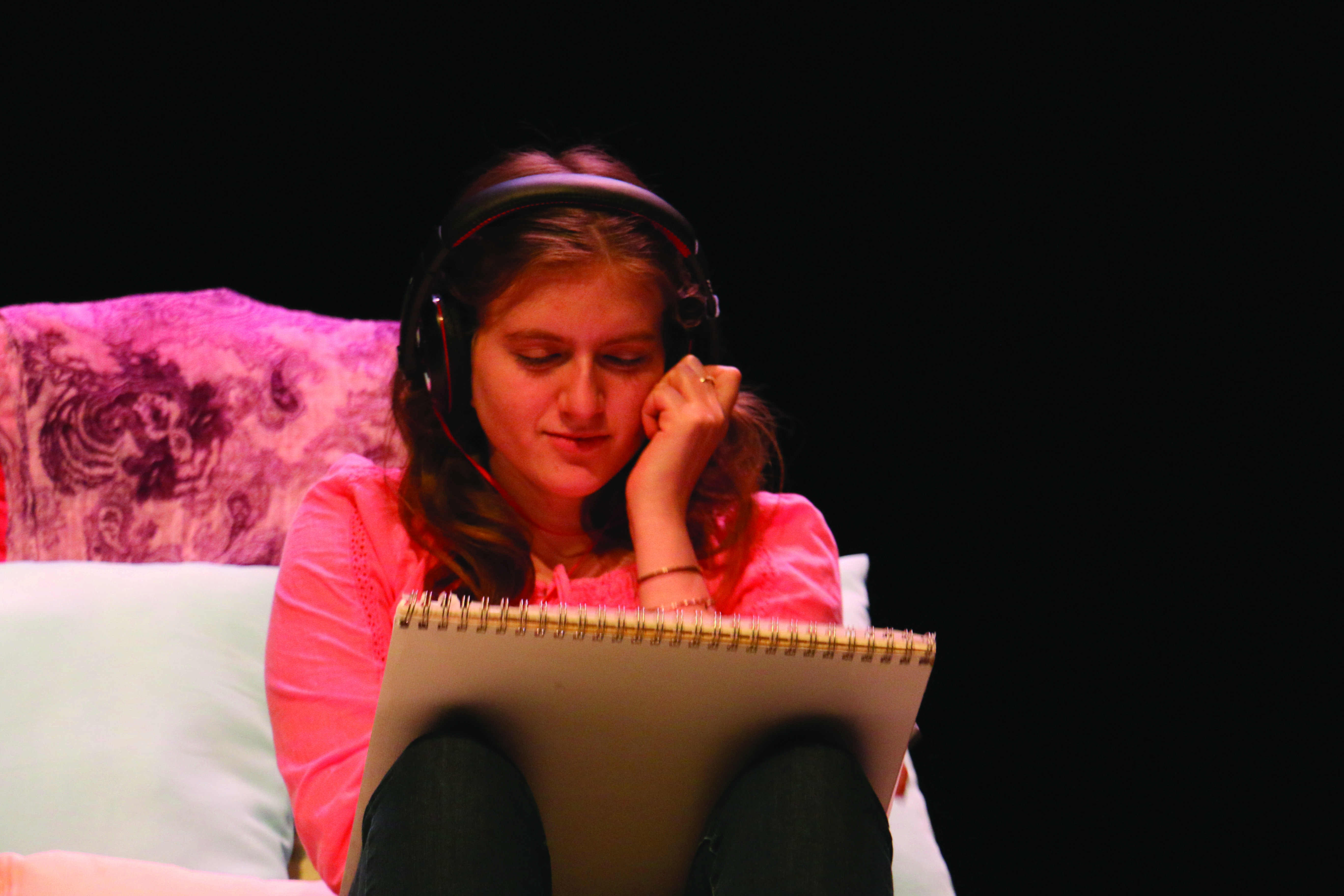 """ISOLATED: Cate Wolfen '17 sits on her bed listening to music during Sabrina de Brito's '17 play, """"The Hidden Empire."""" Credit: Pavan Tauh/Chronicle"""