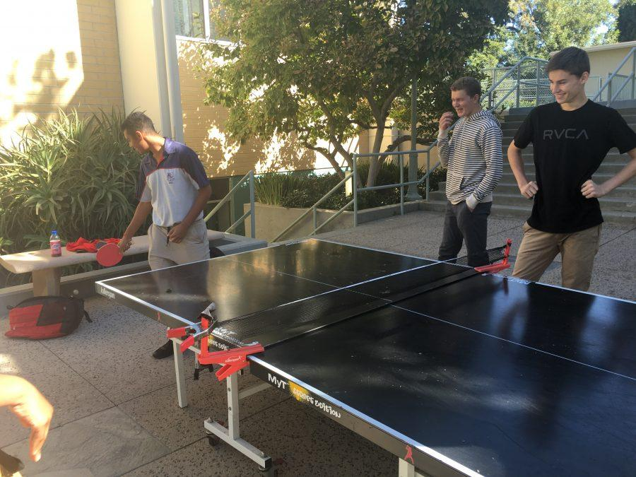 A student from the Westville Boys' High School in South Africa plays table tennis while Harvard-Westlake students watch. Credit: Jenny Li/Chronicle