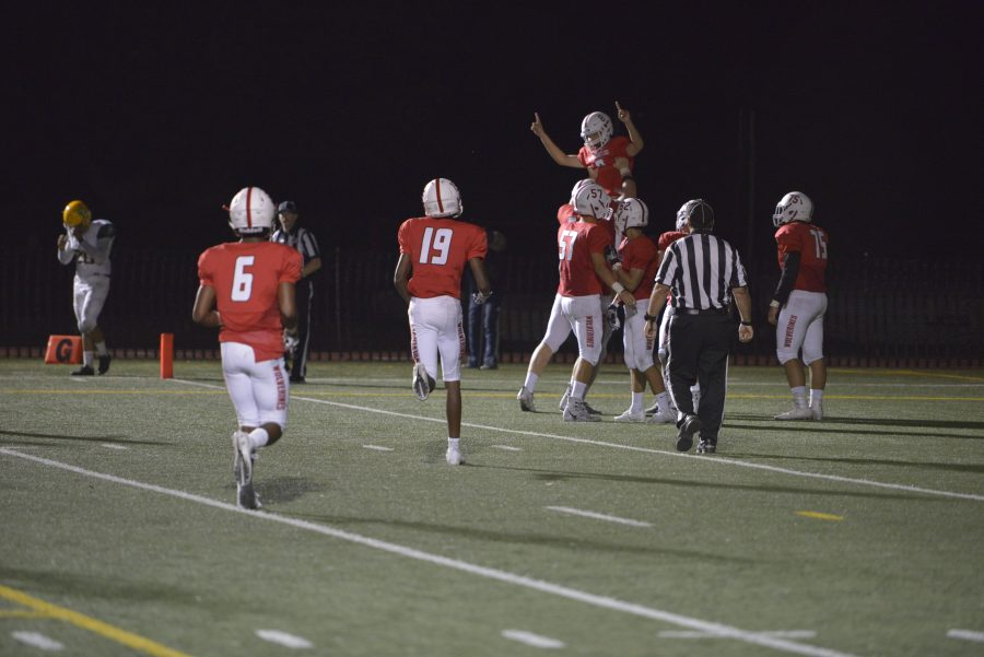Quarterback Jameson Wang 20 celebrates with teammates after his second rushing touchdown of the day. Credit: Jackie Greenberg/Chronicle