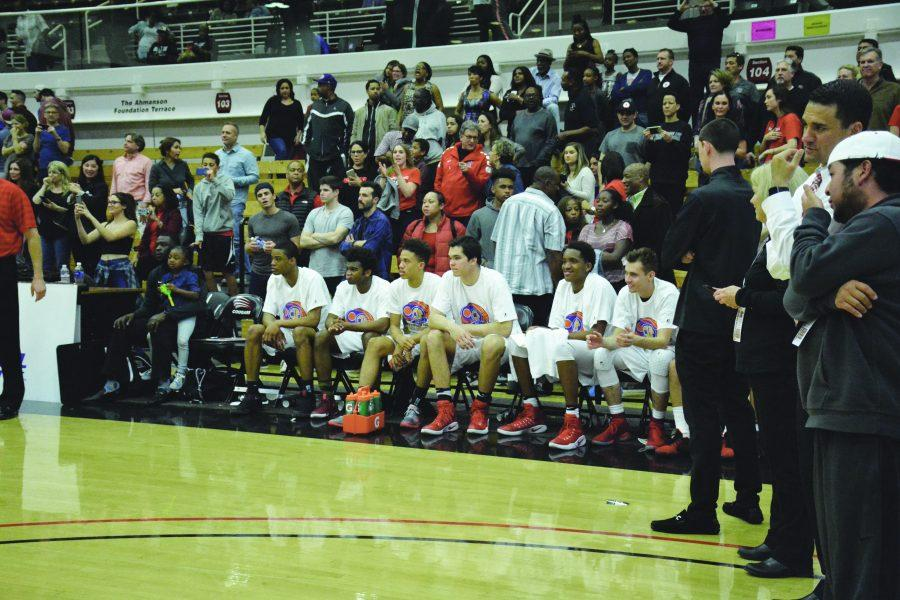 Members of the basketball team sit on the bench during  a game last year. Printed with permission of HW Athletics
