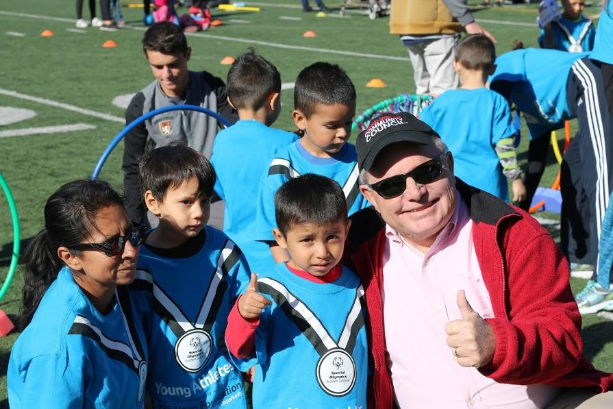 Chaplain J. Young poses with a group of children during the Special Olympics event in Dec. 2016. Young has worked as the Chaplain for the Upper School for the past 21 years. Credit: Pavan Tauh/Chronicle
