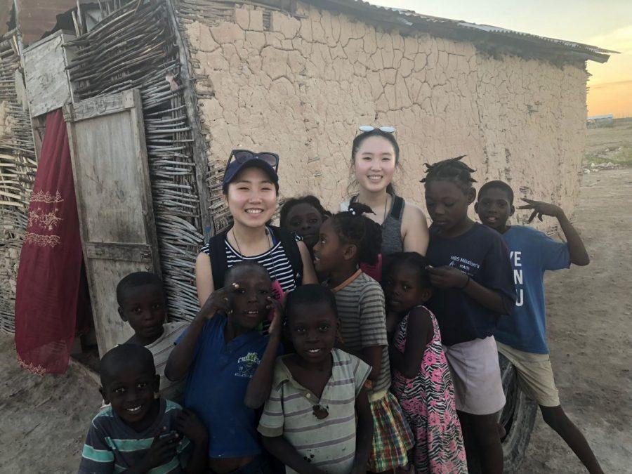 Eliza Yoon '19 and Samantha Yoon '18 pose with the children they met while volunteering in Haiti in January. Eliza Yoon raised money through her company The Cupcake Communities where she sells cupcakes and used the money to build latrines.