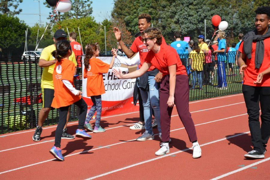 Helen Graham '20, Thomas Glover '18 and Mikey Corrin '18 high five athletes after they race at the Special Olympics. Credit: Alex Goldstein/Chronicle