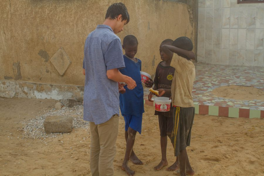 Alec Katz '19 gives bread to the Talibés, or street youth, for breakfast before they start their  morning studies in Saint-Louis, Senegal. His entrepreneurial venture will benefit these youth after graduation, so they have shoes to start businesses. Credit: Alec Katz '19