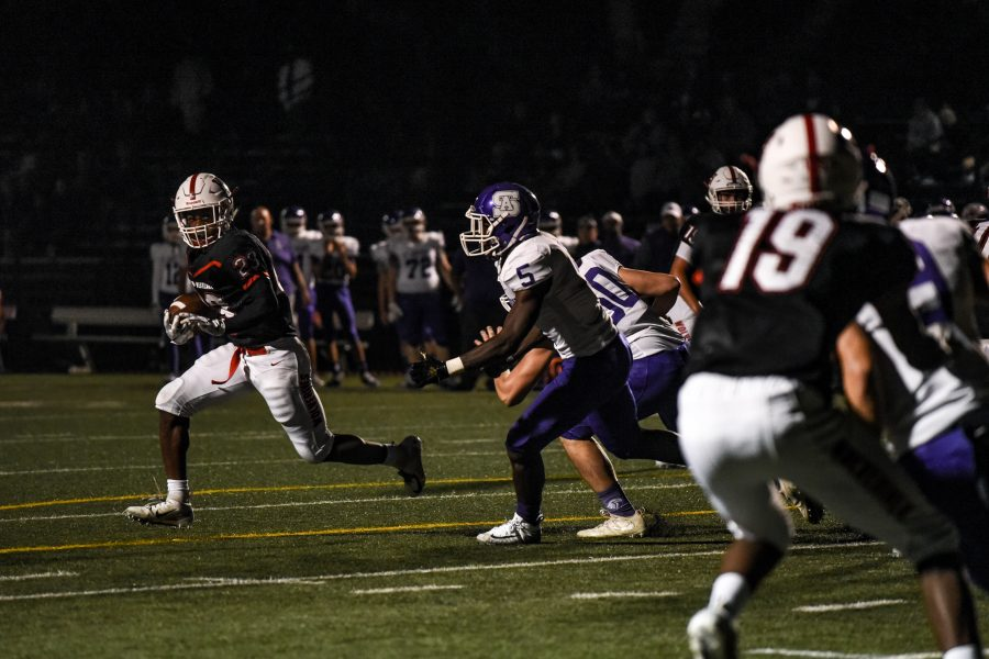 Running back Sultan Daniels '19 dodges Saints defenders during Homecoming victory. Photo credit: Ryan Albert/Chronicle