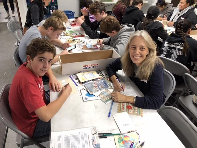 Students and parents write holiday cards to troops at the community service event Saturday. Credit: Kairavi Daum (Maddy '17, Alex '20, Isabella '23)