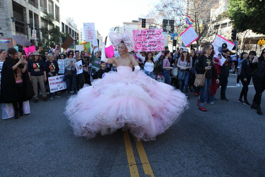 A male protester, donned in a statement dress with anti-Trump messages, participates in the third annual Women's March Saturday.  Credit: Caitlin Chung